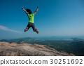 jumping on rocky mountain peak  30251692