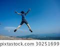 jumping on rocky mountain peak  30251699