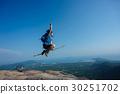 jumping on rocky mountain peak  30251702