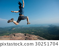 jumping on rocky mountain peak  30251704