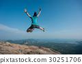 jumping on rocky mountain peak  30251706