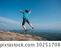 jumping on rocky mountain peak  30251708
