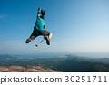 jumping on rocky mountain peak  30251711