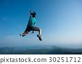 jumping on rocky mountain peak  30251712