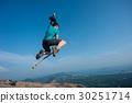 jumping on rocky mountain peak  30251714