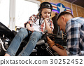 Decent attentive mechanic deciding which wrench to 30252452