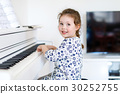 Beautiful little kid girl playing piano in living 30252755