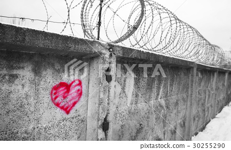 red heart painted on a concrete wall, against  30255290