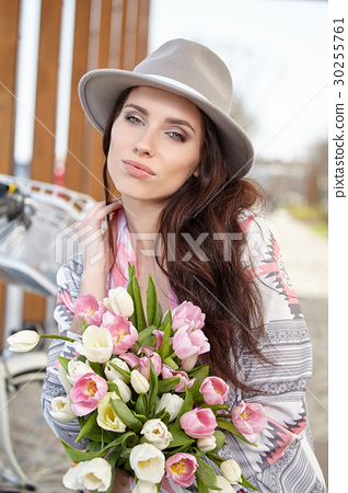 Beautiful young woman on bike in city street 30255761