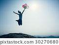 woman jumping on mountain top with balloons 30270680