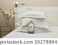 Alarm Clock on a Bed with Pillows 30278864