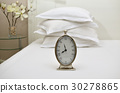 Clock and Pillows on a Bed 30278865