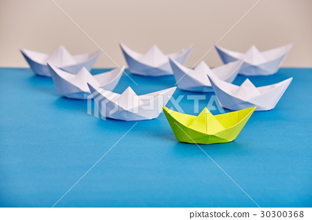 Bright yellow paper ship leading white ones based 30300368