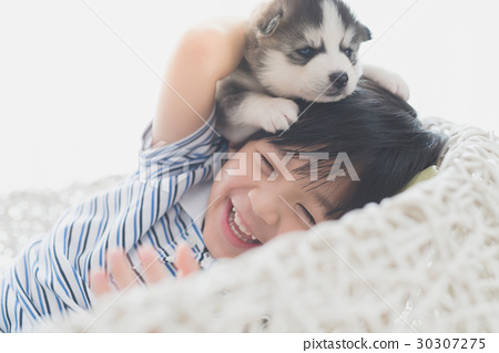 Cute asian child playing with siberian husky puppy 30307275