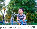 Sad Asian kid riding seesaw board at playground 30327700