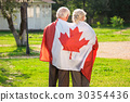 Old couple wrapped in flag. 30354436
