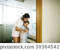 Mother teaching and helping the son how to brush his teeth 30364542