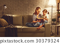 Family before going to bed mother reads to her child daughter bo 30379324