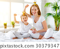 Happy family mother and child daughter playing with crowns in pr 30379347