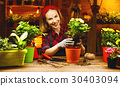 Happy woman gardener transplants and watering flowers 30403094