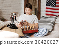 Infatuated with playing boy looking at his toy 30420027
