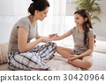 Glad mother applying ointment on the daughters 30420964