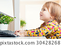 Happy toddler girl typing on her computer 30428268
