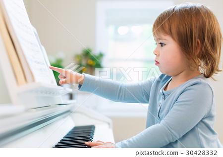 Toddler girl playing piano 30428332