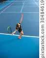The young girl in a closed tennis court with ball 30484619