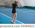 The young girl in a closed tennis court with ball 30484621