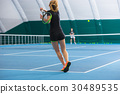 The young girl in a closed tennis court with ball 30489535