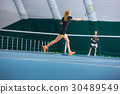 The young girl in a closed tennis court with ball 30489549
