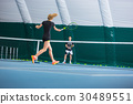 The young girl in a closed tennis court with ball 30489551
