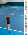 The young girl in a closed tennis court with ball 30489767