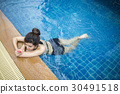 beautiful woman relaxing on the swimming pool 30491518