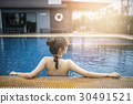 beautiful woman relaxing on the swimming pool. 30491521