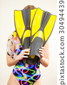 Woman covering her face with flippers having fun 30494439