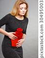 Girl having stomach ache, holding hot water bottle 30495003