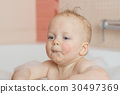 Funny baby with pressed lips in a bathtub. 30497369