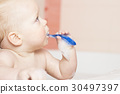 Funny baby boy brushes his teeth.  30497397