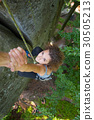 Girl climbing on big rock and hanging on the hand 30505213