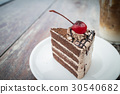 chocolate cake with cherry topping in outdoor cafe 30540682