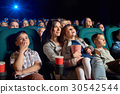 Children with parents enjoying a movie together at 30542544