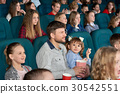 Children with parents enjoying a movie together at 30542551