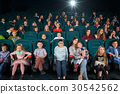 Children with parents enjoying a movie together at 30542562