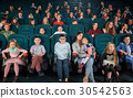 Children with parents enjoying a movie together at 30542563