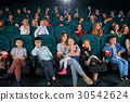 Children with parents enjoying a movie together at 30542624