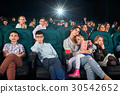 Children with parents enjoying a movie together at 30542652