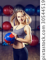 Young fitness girl standing with medicine ball 30544519