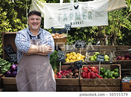 Greengrocer selling organic fresh agricultural product at farmer market 30555379